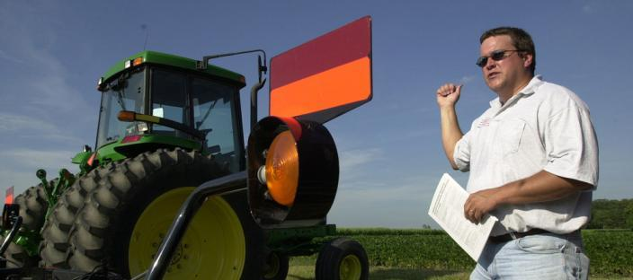 Field day presenter standing next to a tractor in a field