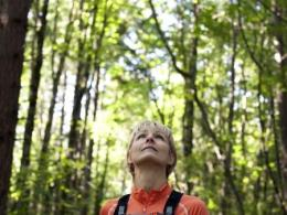 woman looking up at trees in forest