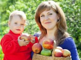 Photo of woman holding toddler boy and basket of apples