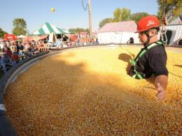 Man standing in a corn bin with audience watching a demostration