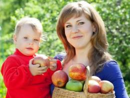 Woman carrying a child and carrying a basket of apples
