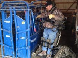 Photo of a farmer in an all-terrain track chair working in a barn.