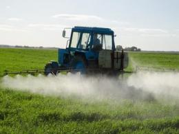 Photo of a field being sprayed by a boom sprayer on a tractor.