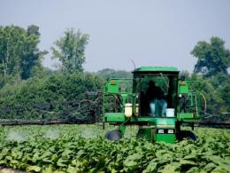 Photo of a farmer in a tractor spraying a field. Photo by Thinkstock