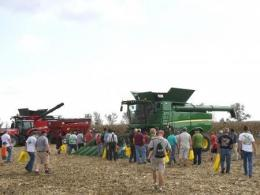 Photo of a group of people watching a green combine demonstrating a corn harvest.