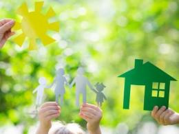 Photo of a small hand holding a paper sun, two small hands holding a paper cut out family and one small hand holding a green paper cut out house with green leaves faded in the background. Photo by I Stock.