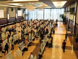 Photo of a large room with educational posters lined up on tables. Photo by Molly Bean.