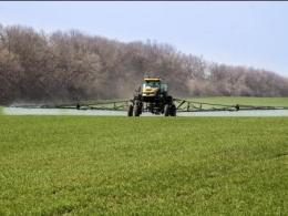 Photo of a green field with a large sprayer spraying the field