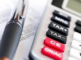 Photo of a pen and calculator laying on a financial document