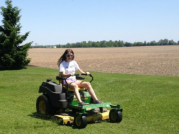 Photo of a young girl mowing grass beside a brown field on a zero turn law mower